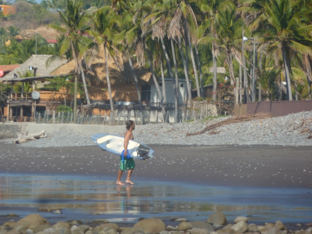 Surfer on the black sand beach - El Tunco, El Salvador