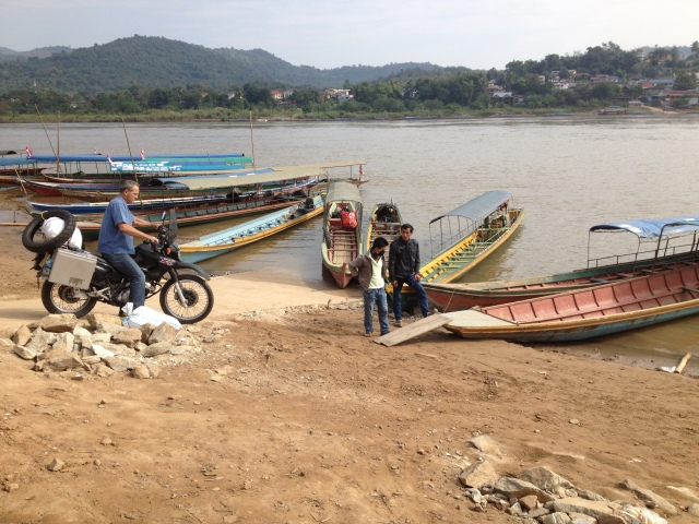 loading the bike onto a long boat - Mekong River, Thailand